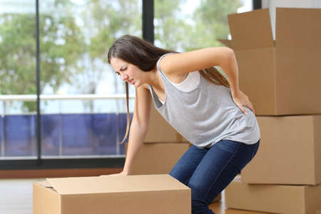 Photo for Woman in pain moving boxes suffering backache grabbinng lumbar area at home - Royalty Free Image