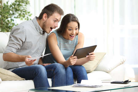 Photo pour Excited couple checking tablet and receipts sitting on the sofa in the living room at home - image libre de droit
