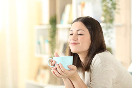 Photo pour Satisfied woman relaxing holding coffee mug sitting on a couch in the living room at home - image libre de droit
