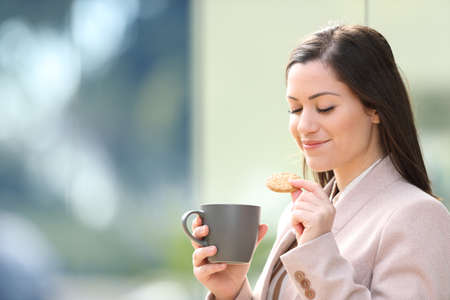 Photo for Entrepreneur eating cookie and drinking coffee at breakfast standing on the street - Royalty Free Image