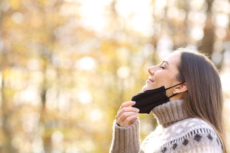 Photo for Side view portrait of a satisfied woman relieving taking off protective mask to breath fresh air in fall season in a park - Royalty Free Image