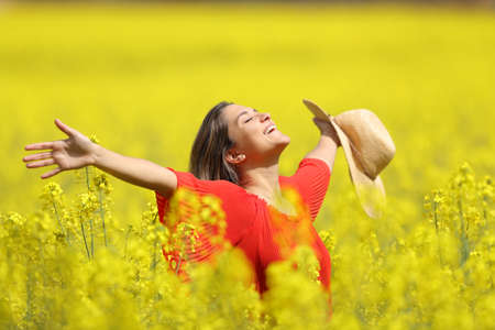 Photo for Happy woman celebrating vacation holding pamela stretching arms in a yellow field - Royalty Free Image
