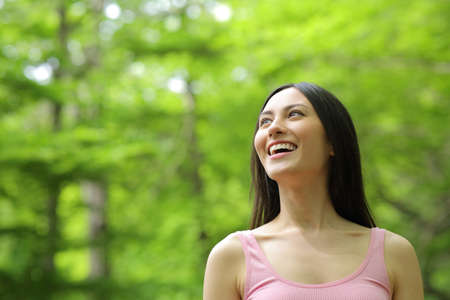 Photo for Amazed asian woman walking looking up and laughing in a forest - Royalty Free Image
