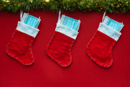 Photo for Horizontal color image with an overhead view of a christmas decoration with Coronavirus on a red background, christmas socks, face masks and hydroalcoholic gels. Covid concept on christmas. - Royalty Free Image