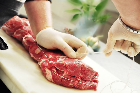 Detail of Hands that Tie Roast Meat on cutting board