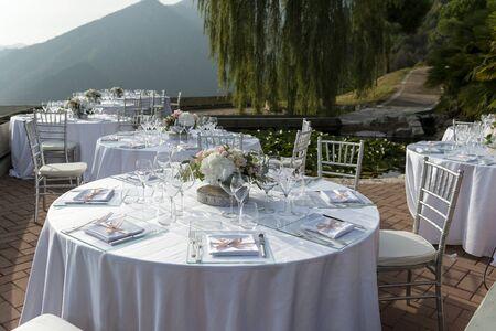 Photo pour Tables set in white for outdoor wedding banquet - image libre de droit
