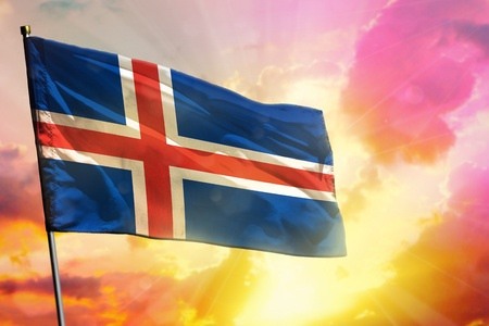 Fluttering Iceland flag on beautiful colorful sunset or sunrise background. Iceland success and happiness concept.