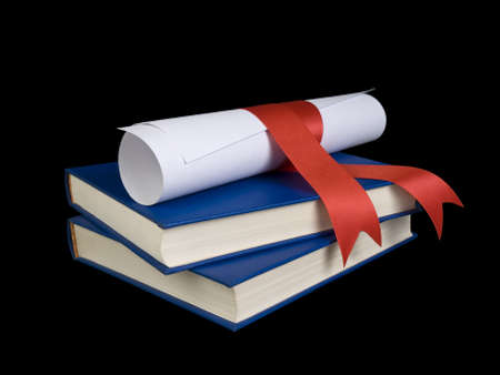 A diploma with red ribbon over blue books.