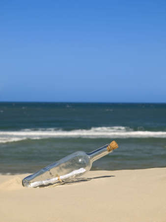 A bottle with a message inside is buried on the beach.