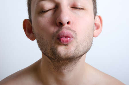Handsome unshaved man ready to be kissed. Close up. Focus on lips.