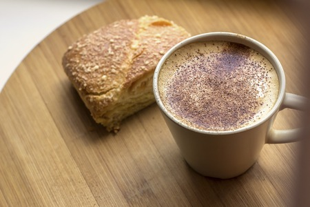 a cup of cappuccino coffee with a fragrant hot bun