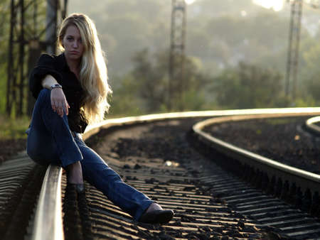 Young blond woman in casual dress sitting on rail