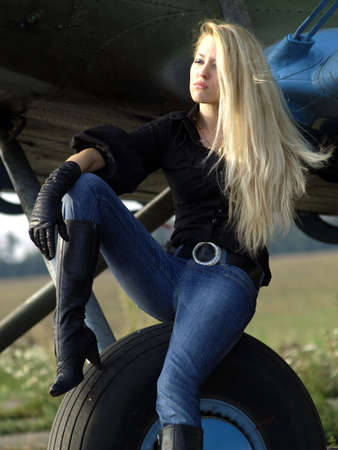 Young blond woman sitting on vintage airplane landing gear