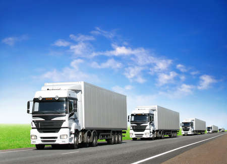 caravan of white trucks on country highway under blue sky