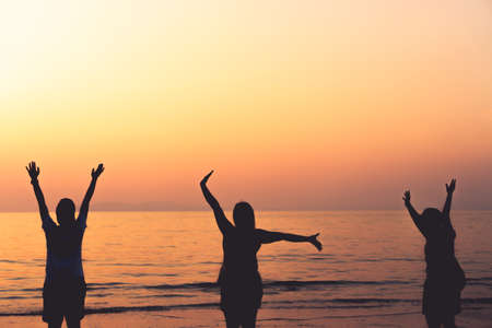 Photo for A group of womans rise hands up to sky freedom concept with blue sky and summer beach sunset background. - Royalty Free Image