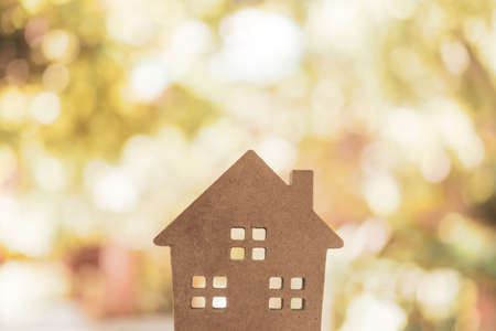 Photo pour Closed up tiny home model on floor or wood board with sunlight green bokeh background. Deam life have own house property for living or investment concept. - image libre de droit