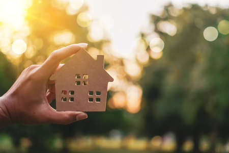 Photo pour Copy space model of a little house that woman holds it background. Deam life have own house property for living or investment concept. - image libre de droit