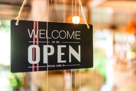 Photo for A business sign that says open on cafe or restaurant hang on tree at entrance of shop with sun light bokeh background - Royalty Free Image