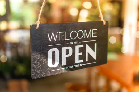 Foto de A business sign that says open on cafe or restaurant hang on tree at entrance of shop with sun light bokeh background - Imagen libre de derechos