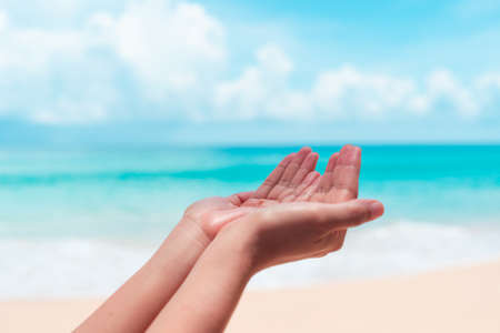 Photo for Woman hands place together like praying in front of nature clean beach and blue sky  background. - Royalty Free Image