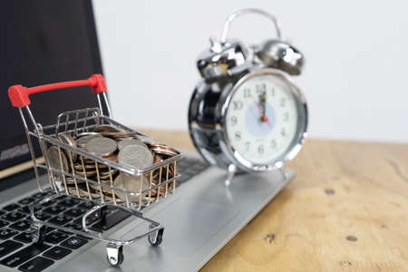 Photo pour Coin in a trolley on a laptop keyboard and alarm clock. Ideas about online shopping, online shopping is a form of electronic commerce that allows consumers to directly buy goods from a seller over the internet. - image libre de droit