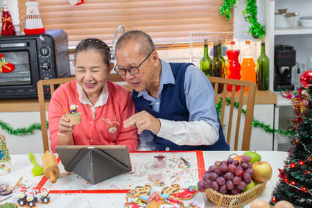Photo pour Senior An Asian grandfather and grandmother wearing aprons learning to make cupcake online with a tablet having fun in a kitchen. - image libre de droit