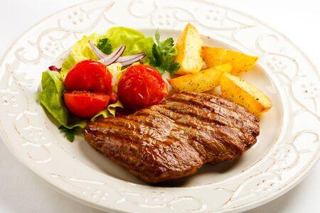 Photo pour Meat grilled potatoes tomatoes greens white background . - image libre de droit