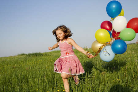 little girl runs with multicolored balloons