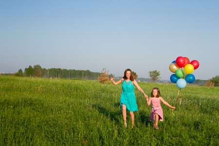 Photo pour Mother and daughter with multicolored balloons - image libre de droit
