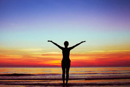healthy lifestyle background, silhouette of woman with raised hands on the beach at sunset