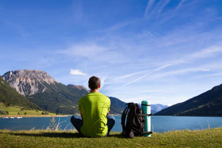 hiking in mountains, young traveller meditate near the lake,  contemplation