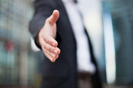 Photo pour Businessman offering for handshake on office buildings background - image libre de droit