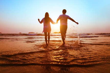 Foto de young happy couple running to the sea at sunset beach - Imagen libre de derechos
