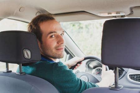 Photo pour portrait of driver in the car or taxi, young caucasian man - image libre de droit