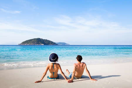 honeymoon destination, young happy couple relaxing on paradise beach