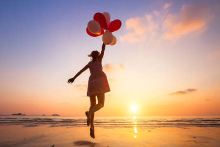 Photo pour imagination, happy girl jumping with multicolored balloons at sunset on the beach, fly, follow your dream - image libre de droit