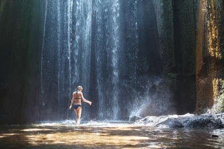 Beautiful waterfall in Bali, woman in bikini bathing and swimming in the water