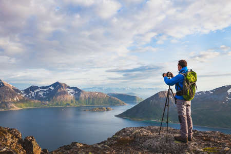 landscape photographer working with tripod and dslr camera in beautiful wild nature, standing with backpack on top of mountain