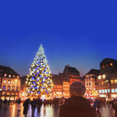 Photo pour christmas market in Europe, decorated xmas tree on the street of city, woman in warm hat enjoying cozy atmosphere - image libre de droit