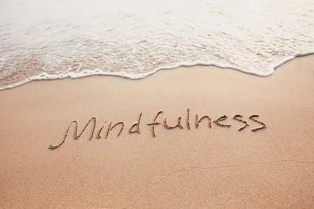 Foto de mindfulness concept, mindful living, text written on the sand of beach - Imagen libre de derechos
