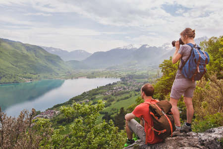Photo pour travel and tourism, couple of travelers with backpacks enjoying panoramic view of lake, hikers relaxing  on top of mountain - image libre de droit