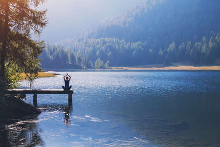 Photo for yoga beautiful background, harmony in life, meditation practice, silhouette of woman sitting in lotus position on the pier of lake and doing breathing exercises in beautiful landscape - Royalty Free Image
