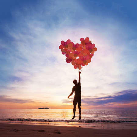 Foto de Kindness and love concept, child flying with heart from balloons. - Imagen libre de derechos