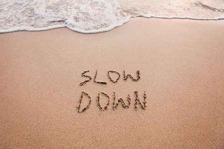 Foto de slow down, mindfulness concept written on sand - Imagen libre de derechos