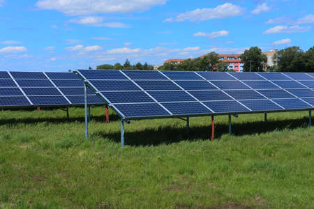 Photo for Solar power plant, blue solar panels on a field with fresh green grass under blue sky with clouds - Royalty Free Image