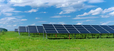 Photo for Solar power plant, blue solar panels on grass field under blue sky with clouds. Solar power generation, renewable energy production - Royalty Free Image