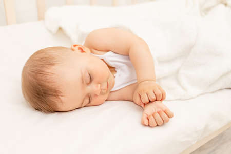 Photo for Small baby girl 6 months old sleeping in a white bed, healthy baby sleep - Royalty Free Image