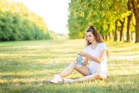 Foto de a pregnant girl does sports in nature in the summer and drinks water from a bottle, yoga for pregnant women in the fresh air - Imagen libre de derechos
