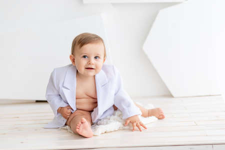 Photo pour a small fat baby six months old in a white jacket and diapers sits on a light background, space for text - image libre de droit