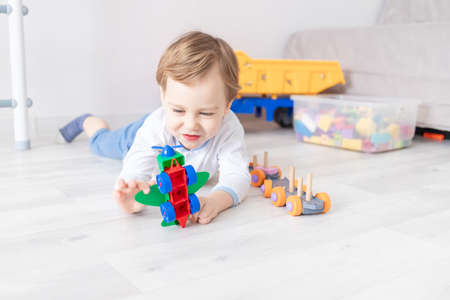 Photo pour baby boy collects the airplane constructor on the floor of the house, the concept of the child's game - image libre de droit